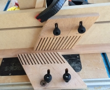 Feather boards holding wood over saw blade
